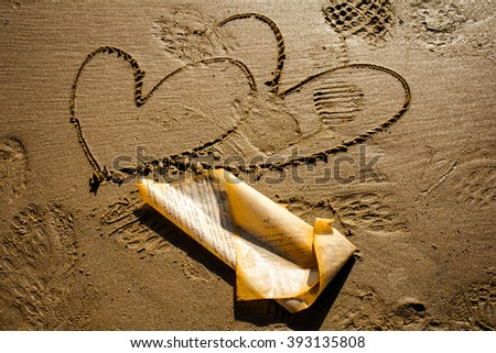 On the beach, the sand is drawn sketch - two hearts. Nearby is a wet sheet of paper.  - stock photo