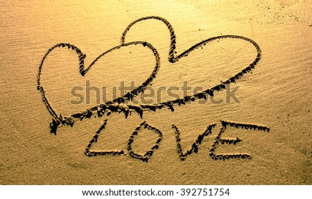 """On the beach, the sand is drawn sketch - two hearts. Written word """"love""""  - stock photo"""