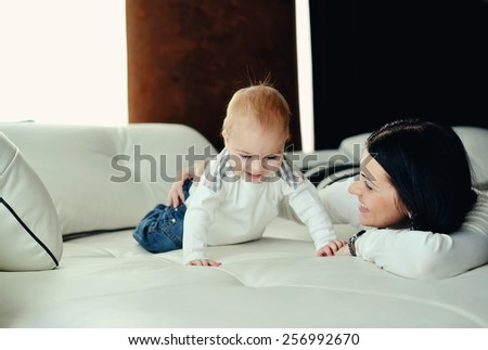 on the bed in the room is small son with red hair with her mother - stock photo