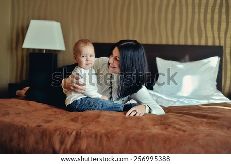 on the bed in the room sitting small son with red hair with her mother - stock photo