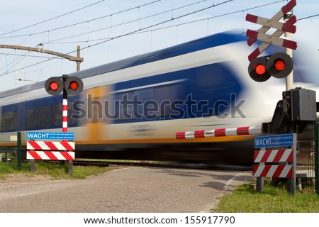 On the blue sign the Dutch text say's: Wait till the red sign stops, there may be another train coming. - stock photo