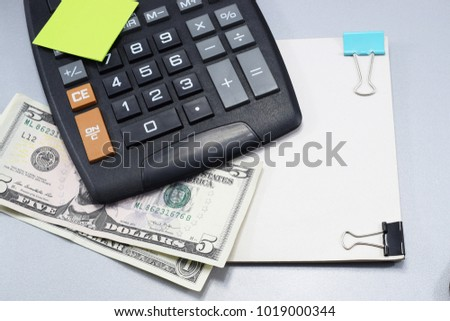 on the desk in the office, a calculator, dollars and a notebook