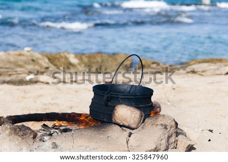 On the fire, fenced with stones in a large pot preparing food for a rest on the sea of people - stock photo