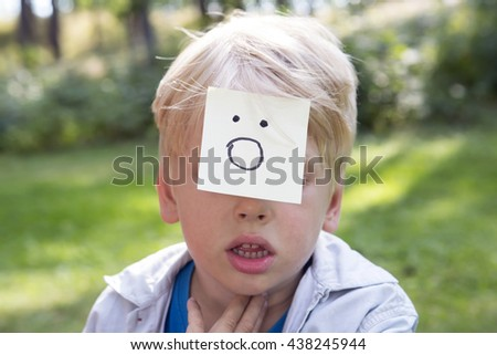 On the forehead shows drawn gasp icon  on yellow stickers. Concept of surprise thoughts and positive emotions. Surprising boy sits on green grass in a forest.   - stock photo