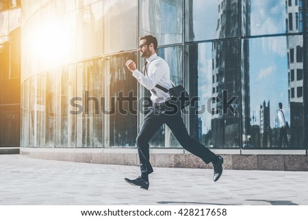 On the go. Full length of young businessman looking forward while running along the street - stock photo
