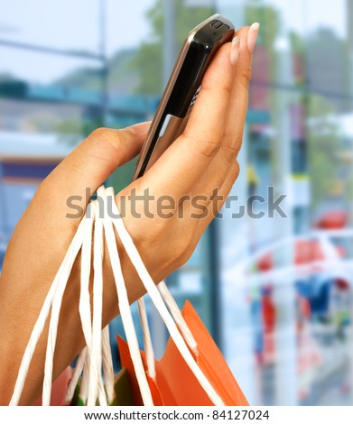 On The Phone After A Shopping Spree With Mall Windows Background - stock photo