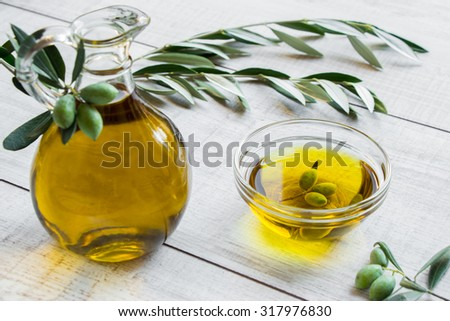 On the right bottle of olive oil to the left bowl with olive oil and olives on the white background of olive tree branches. Olive oil and olives on the white. Horizontal shot. Daylight.   - stock photo