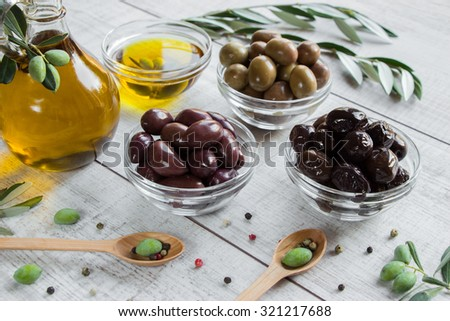 On the right bottle of olive oil to the left 3 bowls with olives, spoons with olives, scattered spices, olive tree branches on wooden white background. 3 different kinds of olives and olive oil.   - stock photo