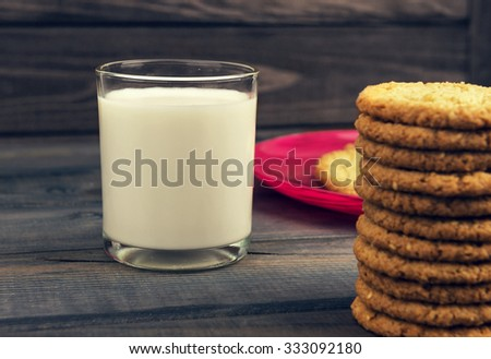 On the rustic wooden table is breakfast - a red glass plate with homemade oat biscuits and a glass of milk - small DoF focus put only to pier - stock photo