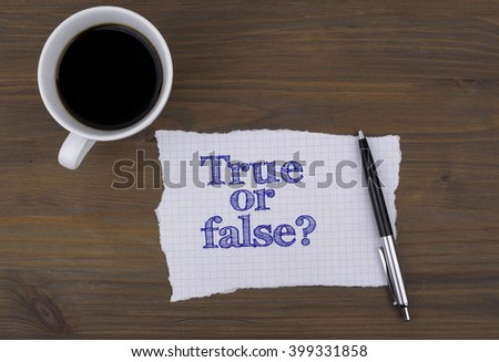 On the table cup of coffee with a piece of paper and text - True or false? - stock photo