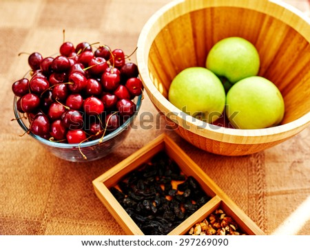 On the table is a form in which lie the nuts and raisins, close to the deep, ? wooden utensils which are apples, ripe cherries in a large glass bowl - stock photo