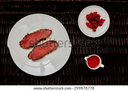 On the table is a plate with two steaks lightly grilled, are served alongside cutlery beside sauce with fresh red berries - stock photo