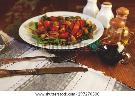On the table is a stylish vintage dish with a salad of fresh leaves, arugula and cheese salad dressed with balsamic vinegar and olive oil - stock photo