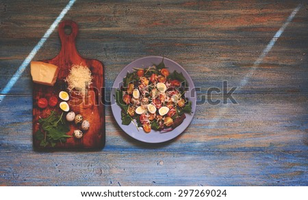 On the table is a vintage blue dish with a light spring salad of tomato, eggs, greens and parmesan salad dressed with oil and balsamic vinegar,standing next to the board which was shredded ingredients - stock photo
