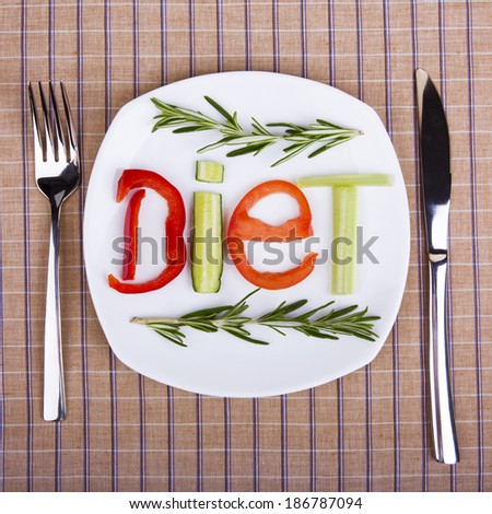 on the table is laid out with white plate on their word - diet - consists of pieces of different vegetables - stock photo