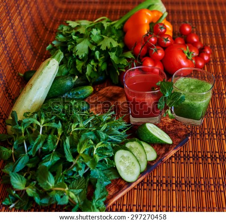 On the table is two cups with fresh juices in the first of tomato and pepper, rub a glass of cocktail in bright green with fresh cucumbers, zucchini and herbs and leek - stock photo