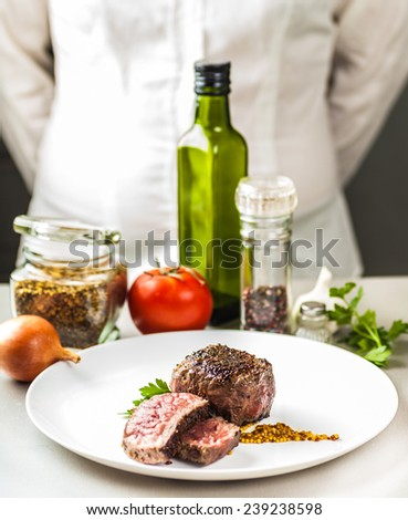 on the table spices, vegetables and a dish of fried medallion on a background of cooks - stock photo