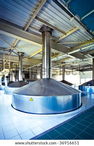 On the territory of brewer's plant with steel fermentation vat - stock photo