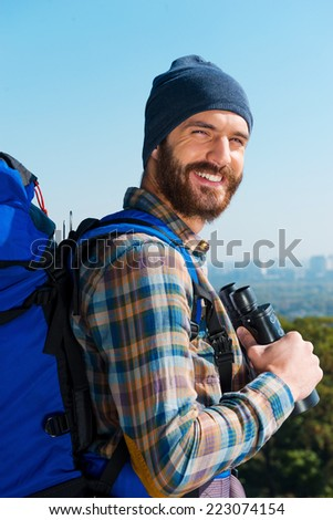 On the top. Handsome young man carrying backpack and looking at camera through the shoulders with smile while standing in the nature and holding binoculars - stock photo