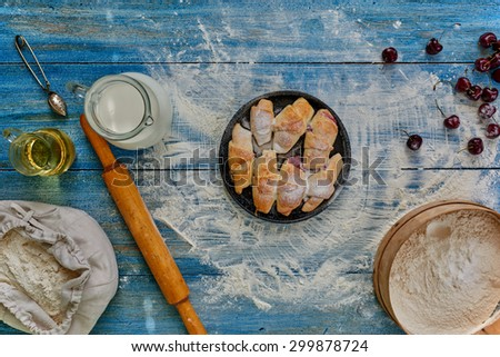 On the vintage wooden table is a round pan on which are laid out bagels with filling sprinkled with powdered sugar, lies near Cherry - stock photo