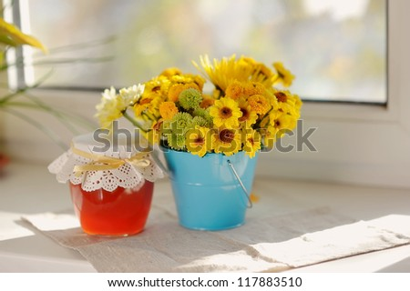 on the window sill in the sun bouquet of yellow flowers and a jar of honey - stock photo