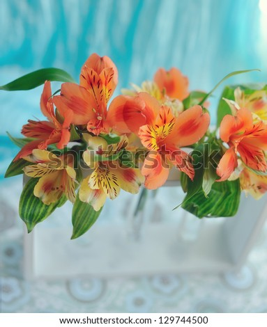 on the window sill with a blue curtain orange spring flowers in a vase - stock photo