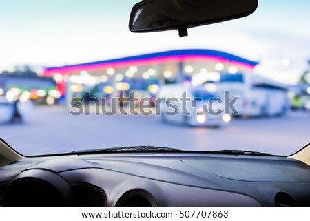 On the windshield , blur image of gas station as background.