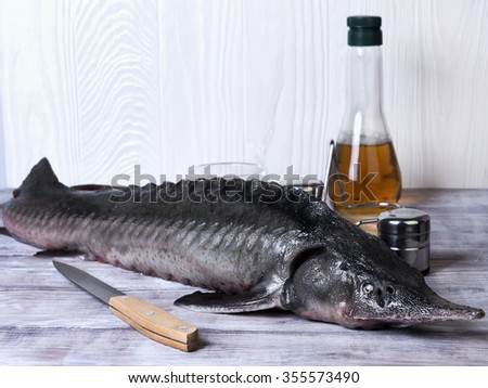 On the wooden background large clear glass dish with a large of whole raw fish sturgeon - stock photo