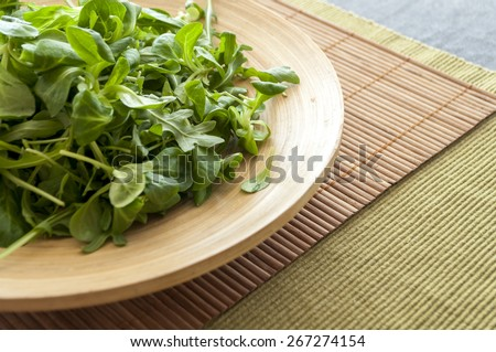 on the wooden plate of lettuce, arugula, close-up - stock photo