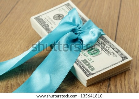 On the wooden table is a stack of hundred-dollar bills in a blue gift ribbons