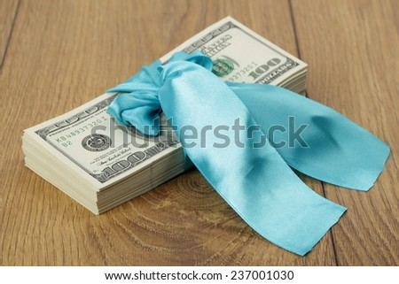 On the wooden table is a stack of hundred-dollar bills in a blue gift ribbons - stock photo