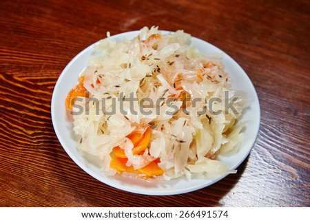 On the wooden table is a white plate with a salad of pickled cabbage with carrot, vegetable oil, seasoning zra Uzbek national, spices, pieces of cabbage shine grain zra condiments - stock photo