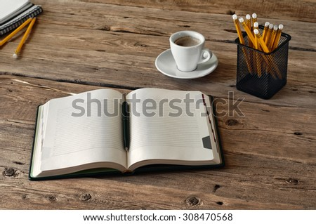 on the wooden table lies a open diary for entries with a cup of coffee and pencils. Top view. Copy space. Free space for text - stock photo