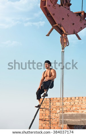 On top of the world. Full length shot of a handsome muscular retro construction worker resting sitting on a ladder near a brick wall