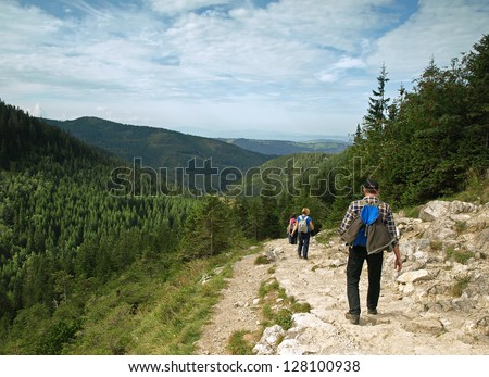 ON TRAIL TO CZARNY STAW GASIENICOWY IN TATRA MOUNTAINS, POLAND - SEPTEMBER 11: Group of tourists walk down from Czarny Staw Gasienicowy on September 11, 2010 in Tatra Mountains, Poland.