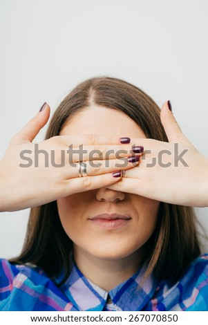 on white background young girl closes eyes with her hands - stock photo