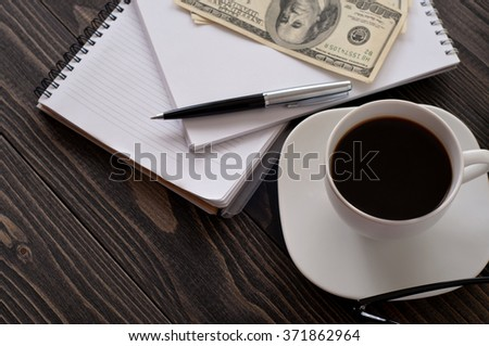 On wooden office desk closeup, stack notepads, pen, cup of coffee and money. top view with copy space - stock photo