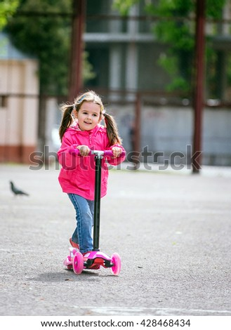 One adorable little girl wearing beautiful clothes riding scooters in a summer city - stock photo
