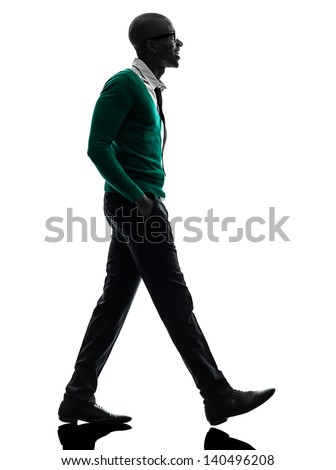 one african  black man walking in silhouette studio on white background - stock photo