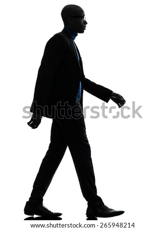 one african black man walking serious in silhouette studio on white background
