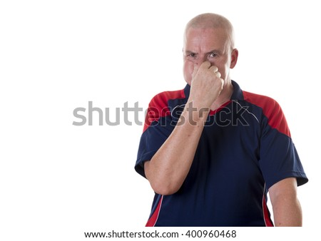 One aging man with shaved head holds his breath and pinches nose with one hand on white background