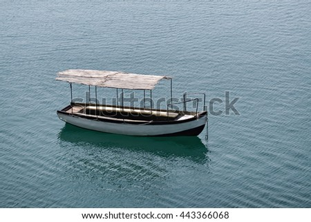 One anchored touristic boat floating in the lake