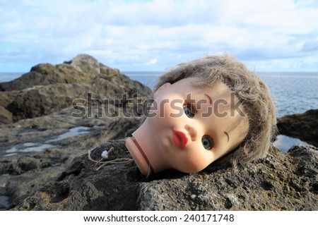 One Ancient Doll's Head Abandoned on the Rocks - stock photo