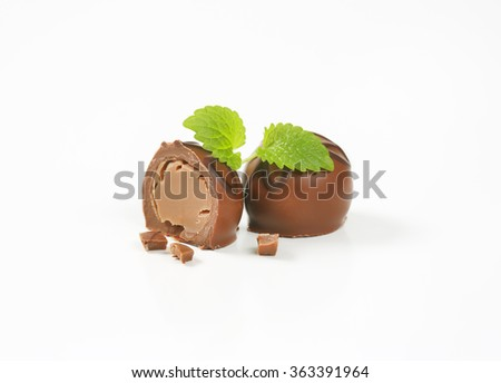one and half belgian chocolate pralines on white background - stock photo