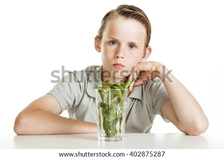 One angry boy wearing sage polo shirt and sitting at a table with a glass placed before him filled with herbs on white background