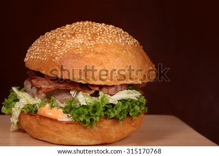 One appetizing big delicious fresh burger with green lettuce red tomato cheese cabbage bacon slice meat cutlet and white bread bun with sesame seeds on black background copyspace, horizontal picture - stock photo
