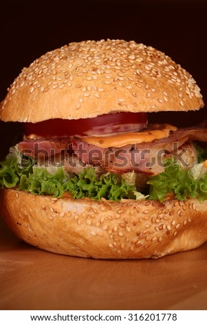 One appetizing big delicious fresh burger with green lettuce red tomato cheese cabbage bacon slice meat cutlet and white bread bun with sesame seeds on black background closeup, vertical picture - stock photo