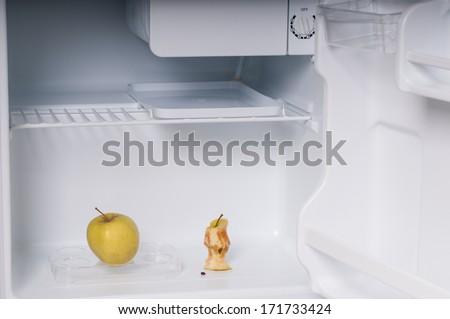 One apple andapple core  in open empty refrigerator - stock photo
