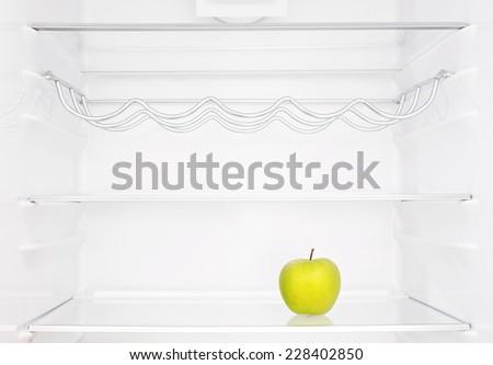 One apple in open empty refrigerator - stock photo