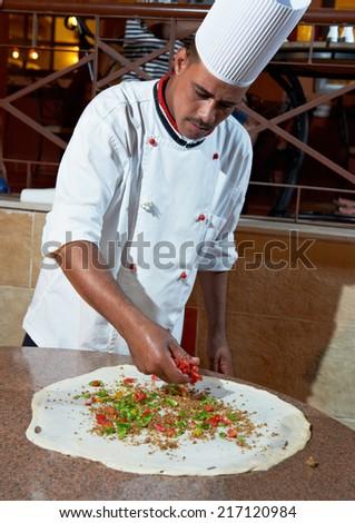 One arab chef baker in white uniform making pizza at kitchen - stock photo